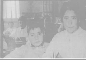 En aquesta foto és veu Dolors Porcalles mestra de l'escola J.J. Ràfols amb un alumne. L'autor de la foto és desconegut.