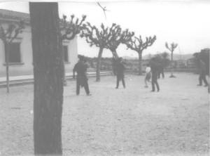 En aquesta foto es veuen els nens jugant a futbol. No tenen portaries,fan servir els arbres de porteries.